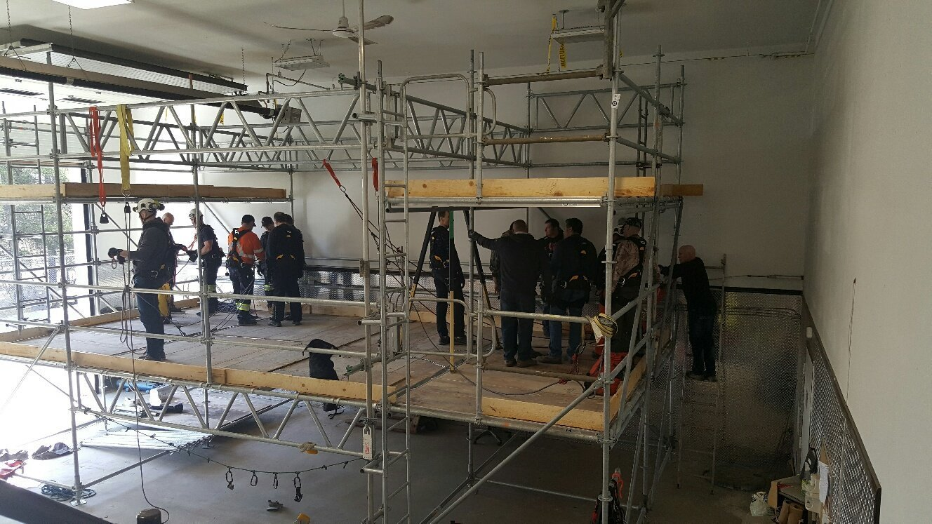 A group of scaffolders working indoors.